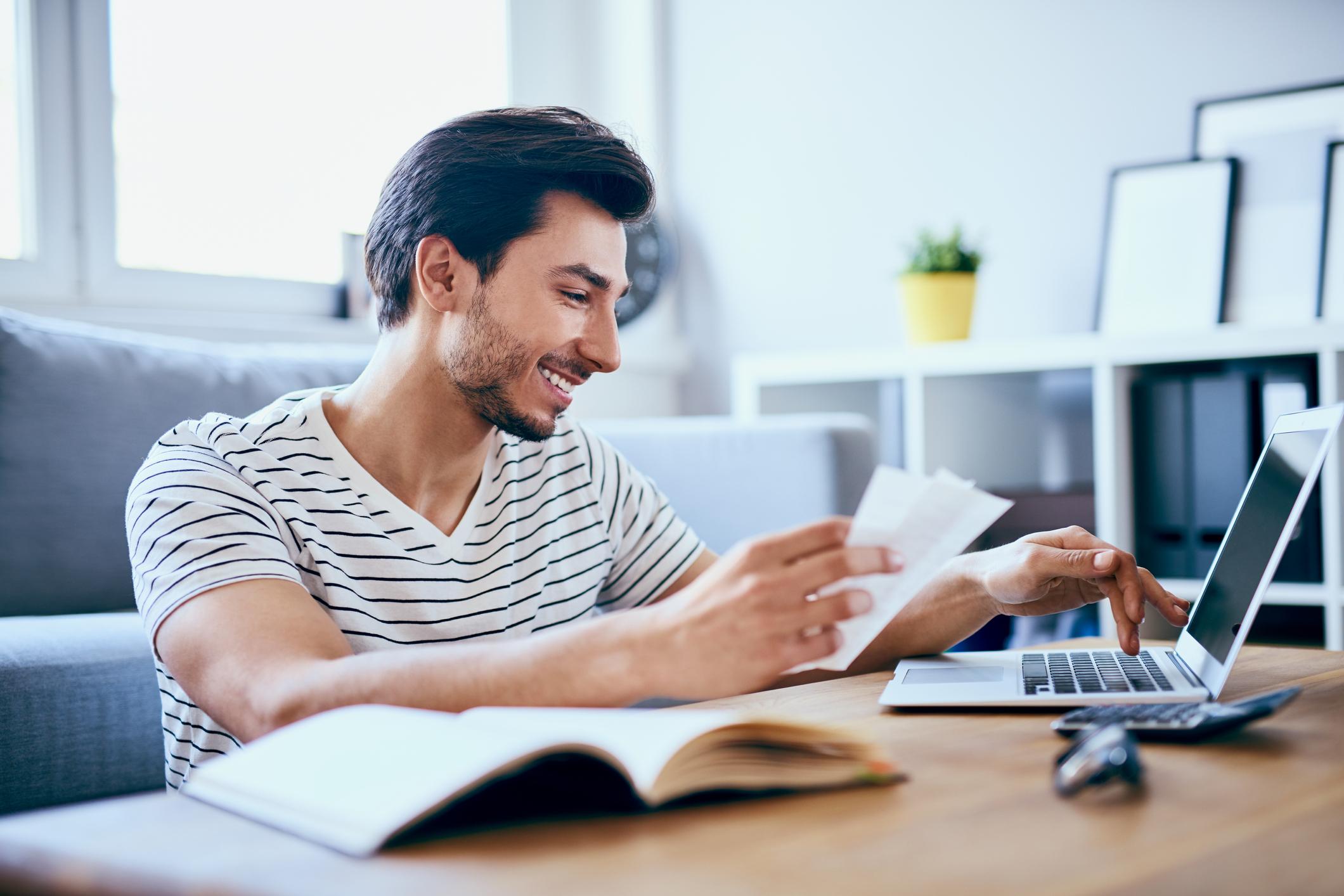 Blije man doet de belastingaangifte online op zijn laptop